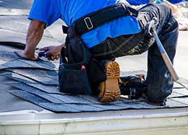 aq contracting worker wearing blue shirt on top of roof installing shingles