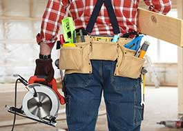 man providing additional services for aq contracting wearing brown tool belt and holding electric saw
