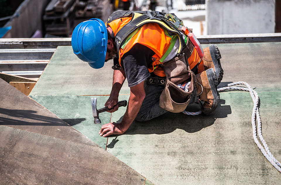 construction worker wearing blue hard hat and orange vest repairing flat commercial roofing