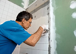 man providing additional services by applying concrete for white bathroom tile