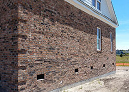 side of house with brown bricks from additional services