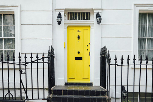 yellow door between about two windows on white house with black fence