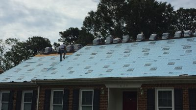 construction worker providing roof replacement service on brick house covered with roofing material