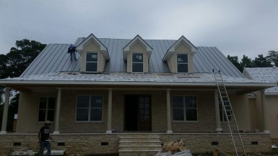 construction workers providing roof replacement services on brick house with light gray metal roof