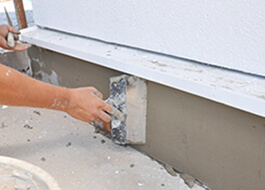 person providing addition services by repairing plaster with short brush