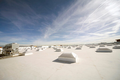 white, TPO rooftop with flat roof installation and generators under blue sky