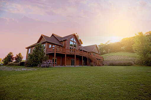 aq contracting style brown, two-story cabin house on green field with trees and sunshine in background